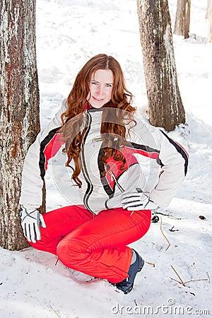 Woman in a sporting suit near a tree in-field