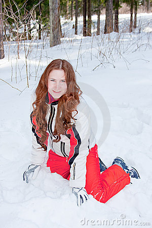 Woman in a sporting suit sits on to snow  in-field