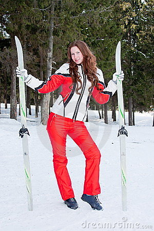 Woman in a sporting suit with skis in-field