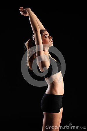 Woman in sports outfit stretching arms above head