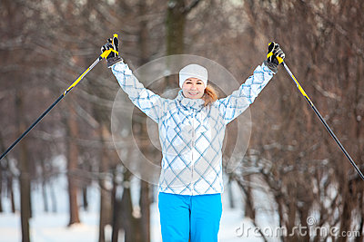 Woman sportsman on cross ski with hands up