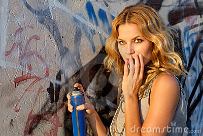 Woman spraying graffiti on a wall