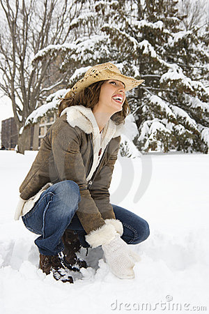 Woman squatting in snow.
