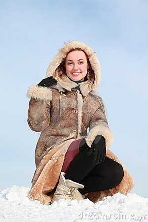 Woman squatting on snow and holds hood hand