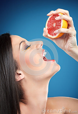 Free Woman Squeezing Orange Into Mouth Royalty Free Stock Images - 27519199