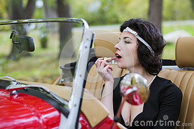 Woman stains the lips before car mirror