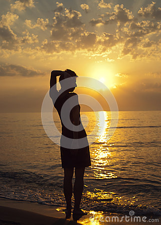 A woman is standing on the beach