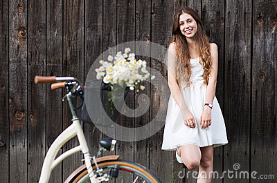 Woman standing with bike by wooden barn