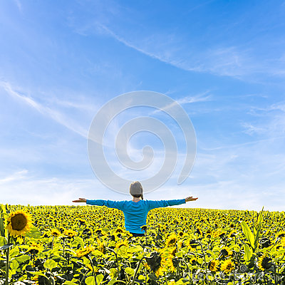 Woman standing in field of sunflowers