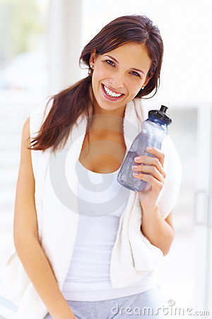 Woman standing in the gym holding a water bottle