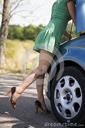 Woman standing by her broken car
