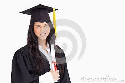 A woman standing with her degree
