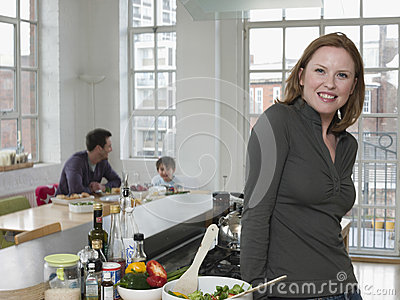 Woman Standing At Kitchen Counter With Family In Background