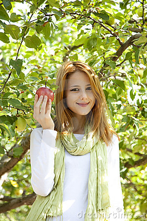 Woman standing near the apple tree.