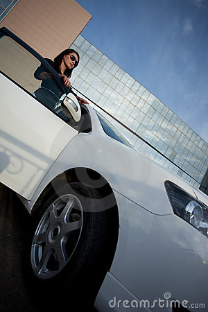 Woman standing near car, wide angle