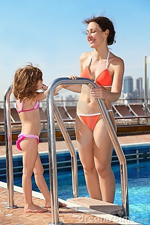 Woman standing near pool and looking at daughter