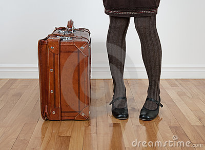 Woman standing near vintage suitcase