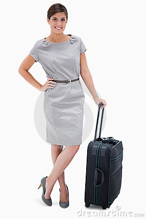 Woman standing next to wheely bag