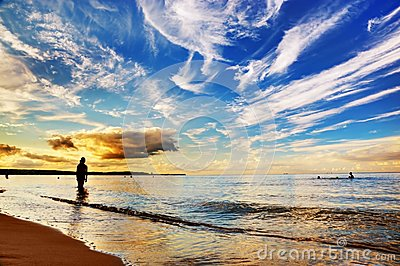 Woman standing in ocean. Dramatic sunset sky