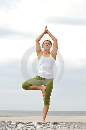 Woman Standing On One Leg In Balance Yoga Pose Royalty