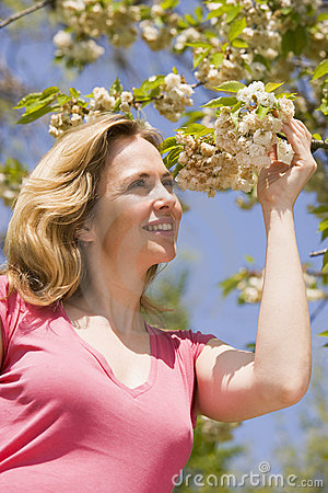 Woman standing outdoors holding blossom smiling