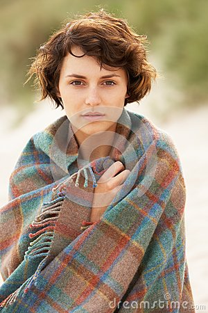 Woman Standing In Sand Dunes Wrapped In Blanket