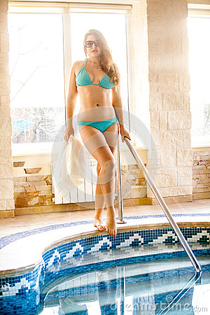 Woman standing at swimming pool in spa center