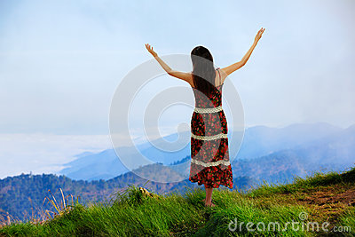 Woman is standing on top of the mountain