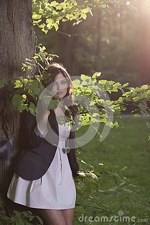 Woman standing in wood on sunny day