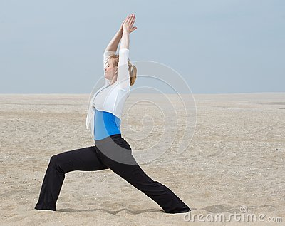 Woman standing in yoga pose at the beach
