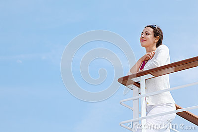 Woman stands on board of ship and rests her hands