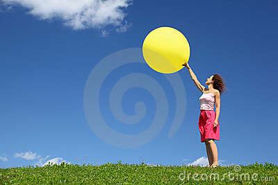 Woman stands on grass and starts inflatable ball