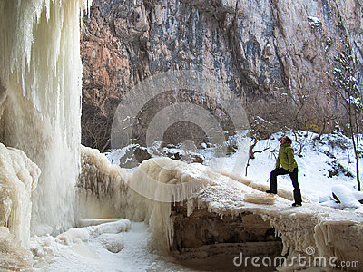 A woman stands on the ice near a waterfall