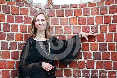 A woman stands near the brick wall