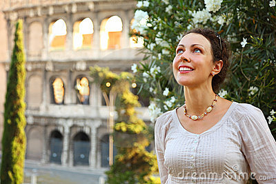 Woman stands near Colosseum and looks up