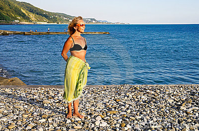 Woman stands on sea coast