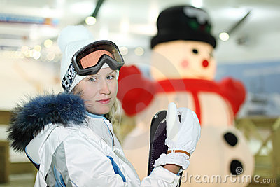 Woman stands with skis in indoor ski