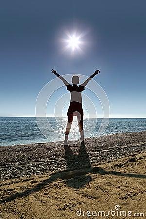 Woman stands on socks ashore opposite sun