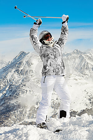 Woman stands throwing up hands with ski poles