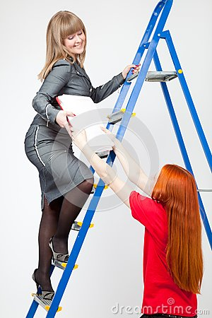 A woman on a stepladder with papers
