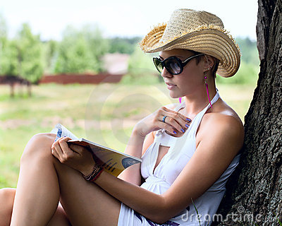 Woman in a straw hat reading a book