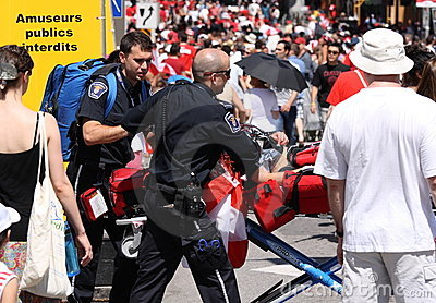 Woman on Stretcher in Crowded Street Editorial Image