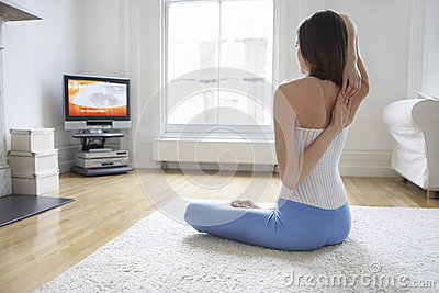 Woman Stretching Arms And Watching TV At Home
