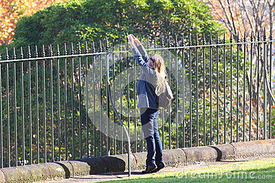 Woman stretching at iron fence