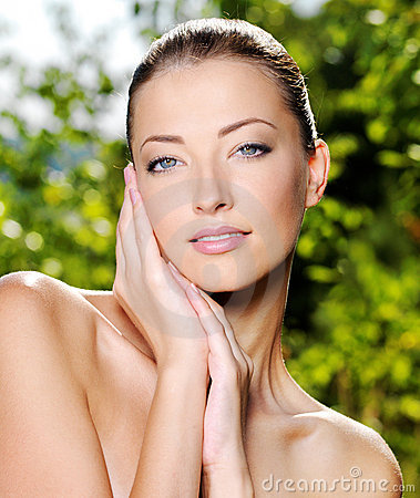 Woman stroking her fresh clean skin of face