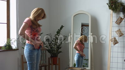 Woman struggling trying to fit into tight jeans stock footage
