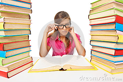 Woman student sitting at the desk surrounded with piles of books
