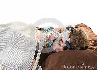 Woman suffering from sleep apnea wearing mask