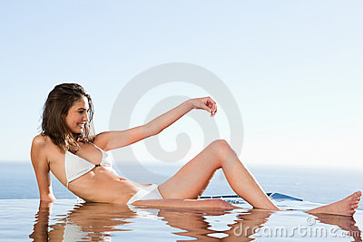 Woman sunbathing on pool edge