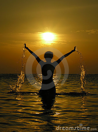 Woman at sunrise with drops of water